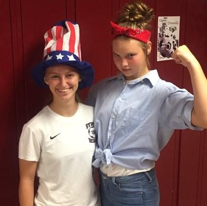 Two High School girls at their lockers dressed for Spirit Week.
