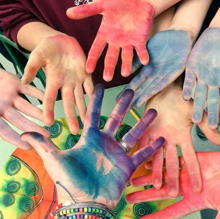 Close-up of a a group of student hands, colored from pastels in art class.