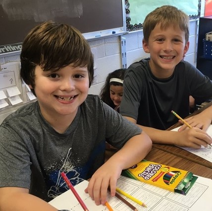 Two smiling boys at the Elementary School studying family trees.