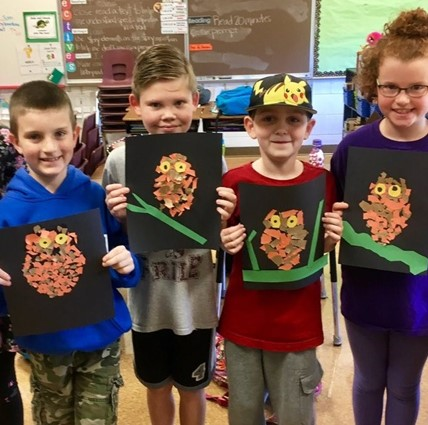 Four Elementary School students displaying their artwork of owls.