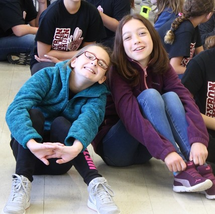 Two ES girls sitting together during assembly.