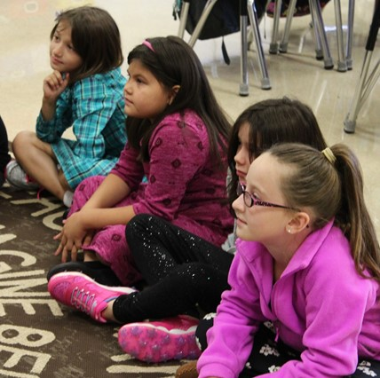 Students sitting on rug listening.
