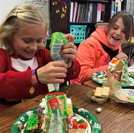 Students making gingerbread houses.
