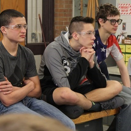 Three High School students in woodworking class.