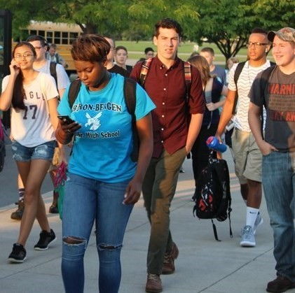 Jr./Sr. HS students coming off the bus, headed into school.