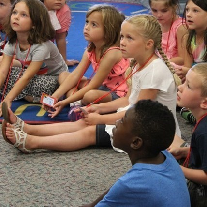 Group of Elementary school children on floor listening intently.