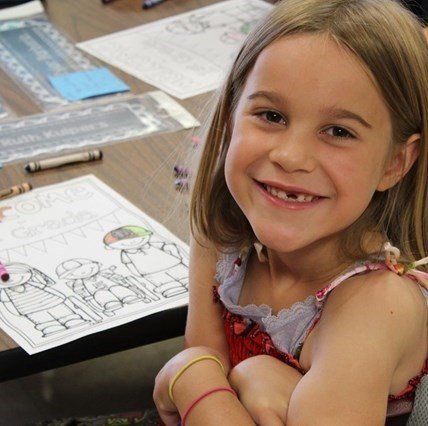 Smiling girl student sitting at her desk at the Elementary School.