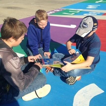 Three boys reading on playground at the Elementary School.