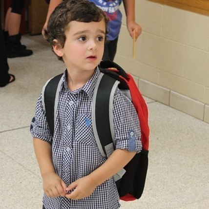 Young boy in the hall of the Elementary School on his first day.