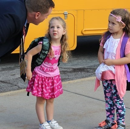 Principal Meister speaking with Elementary School students at the bus loop.