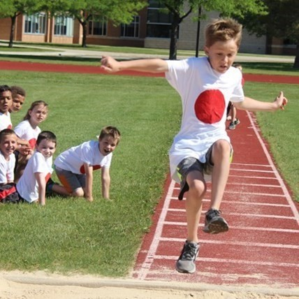 Elementary School boy wearing a tshirt representing Japan while participaing in a long jump during Olympic Day track and field events.