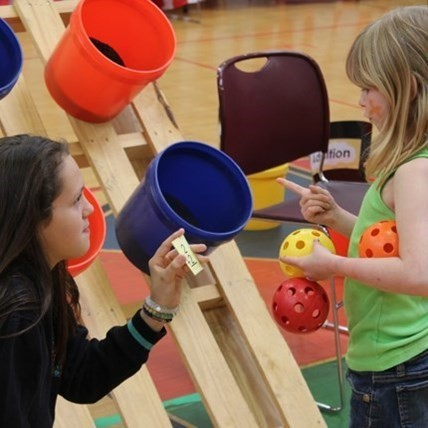Older student helping younger student during Math Carnival event at the Elementary School.