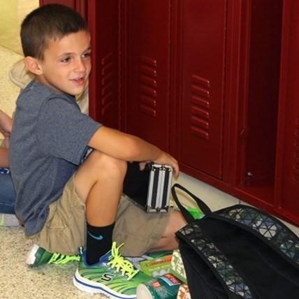 Elementary School aged boy at locker.