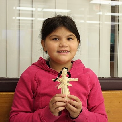 student with corn husk doll