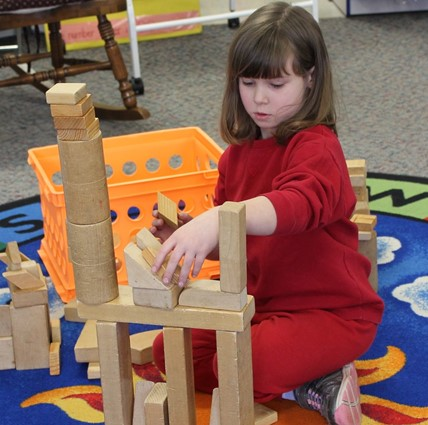 Student working with building blocks on colorful rug.