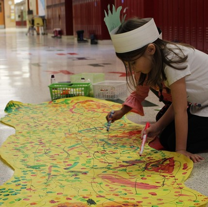 Girl creating large artwork on the floor in the hallway.