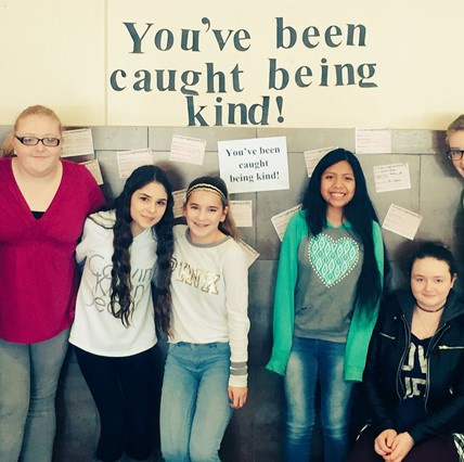 "Jr./Sr. HS students with sign ""You've been caught being kind."""