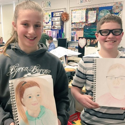 Two students holding self-portraits.