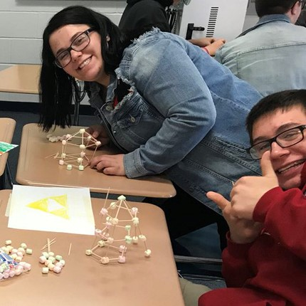 Students smiling while working on projects.