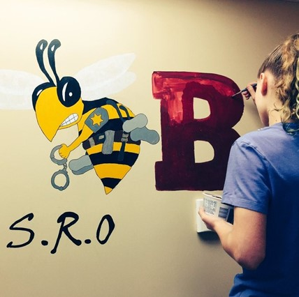 Student painting wall mural of bee.