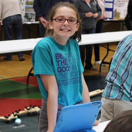 Student at the Science Fair programming robots.