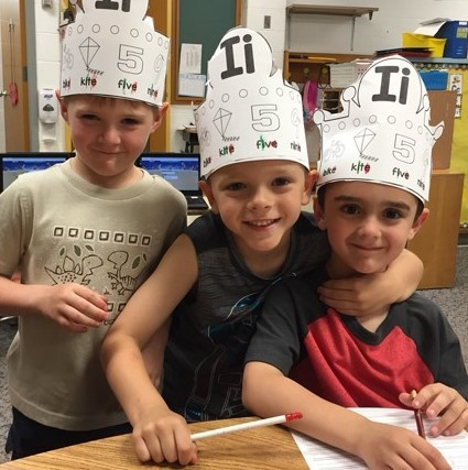 Three kindergarteners learning about vowel sounds.