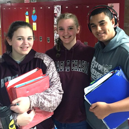 Three students wearing BB Pride gear in the hallway.