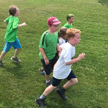 Boys running during field sports at the Jr. Olympics.
