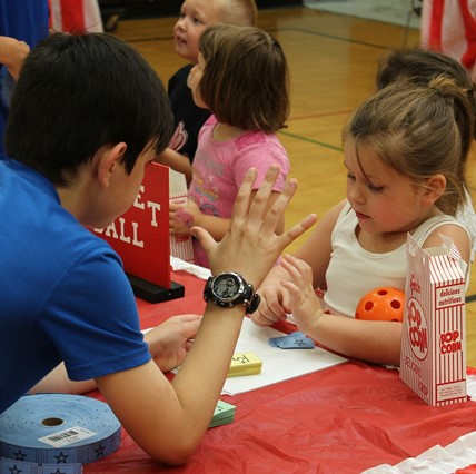Sixth-grader with younger student at Math Carnival.