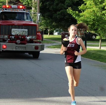 Varsity runner carrying the torch through Bergen during Torch Run.