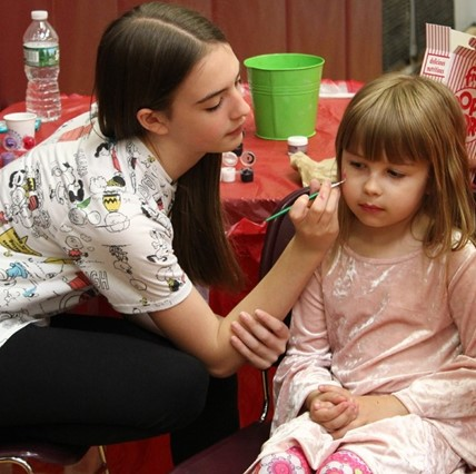Sixth-grader painting younger girl's face at Math Carnival.