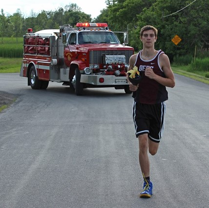 Varsity runner carrying the torch through Bergen during Torch Run.