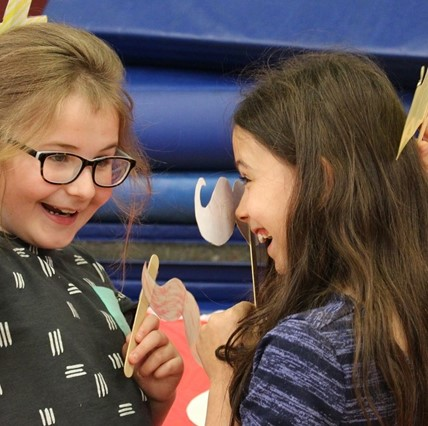 Two young girls having fun with masks at Math Carnival.
