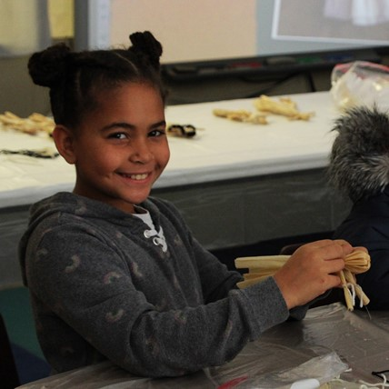 student making corn husk doll