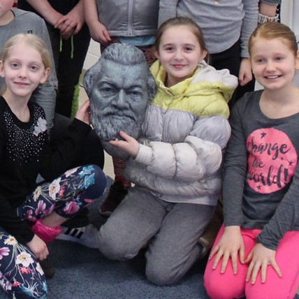 students pose with bust of Frederick Douglass