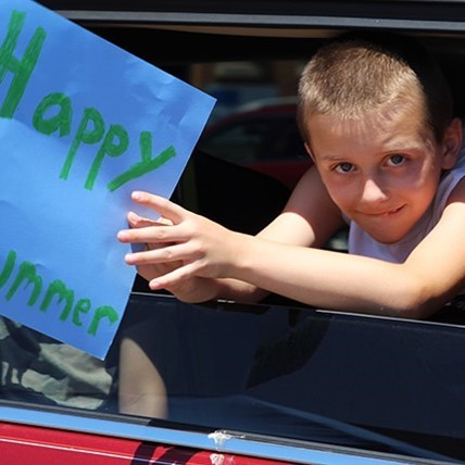 Student with happy summer sign