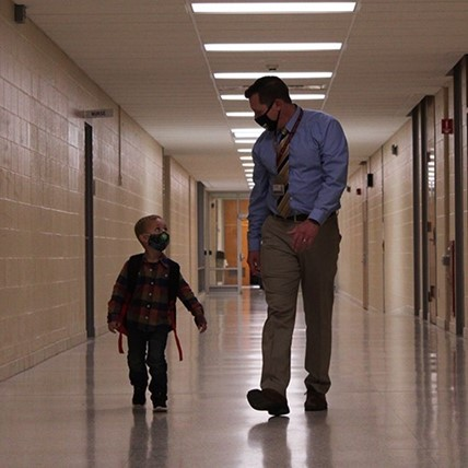 Principal and student in hallway