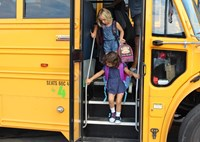 School bus with Elementary School children coming down the steps.