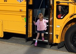 School bus with Elementary School student coming down the steps.